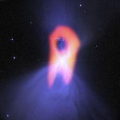 The ghostly Boomerang Nebula, called the 'coldest place in the universe,' reveals its true shape in this image from the giant ALMA radio telescope. The background blue structure, as seen in visible light with the Hubble Space Telescope, shows a classic double-lobe shape with a very narrow central region. Image released Oct. 24, 2013.