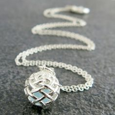 Weave Small Ball Pendant in Silver with a piece of rough Blue Topaz gemstone inside.