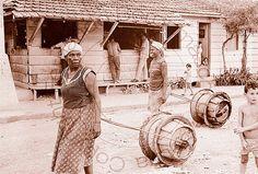 Transporte de água em barril na Favela da Maré em 1970. Rio de Janeiro, Brasil.