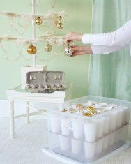Safe Ornament Storage: Martha Stewart's solution.  Glue plastic cups to cut to container size piece of cardboard.  Wrap ornament in acid free tissue paper and place in cup for safe storage.