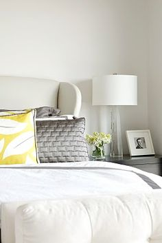 mostly white bedroom, with gray and yellow