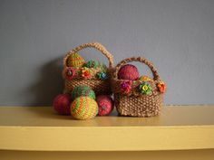 Mini eggs with their own knitted basket decorated with tiny knitted flowers. A pattern for bigger eggs is also included. The eggs are knitted in the round and then stuffed before closing.