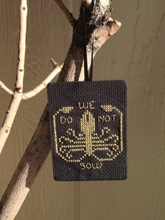 This ornament is hand cross stitched with metallic thread on 14 point Aida cloth. It is on a handpainted black piece of wood which is sealed
