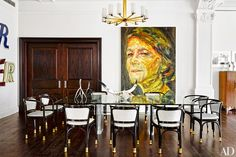 A painting of actress Charlotte Rampling gazes across the dining area; the Jules Leleu chandelier is from Bernd Goeckler Antiques, the Karl Springer table is from Todd Merrill Studio, and the circa-1900 Gustav Siegel chairs were found at Kimcherova.