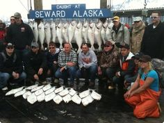 A group of people serving in the military pose in Seward with halibut caught earlier that day during a special appreciation outing, in this photo by Lee Leschper.