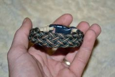 Turk's head bracelet; one strand of tan paracord for the core; one strand of green mini-paracord and one strand of tan mini-paracord for the outer four bight, 23 lead Turk's head.    www.facebook/...