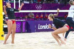 Misty May-Treanor and Kerri Walsh put on a strong performance and defeated Australia's Natalie Cook and Tamsin Hinchley to start their defense of the gold medal in women's beach volleyball.
