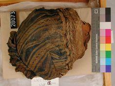 Foto de la cabeza de la mujer desecada con el gorro, encontrados en Hawara , en la exposición del museo Británico.