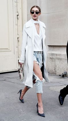 Gigi Hadid wears a white choker top, trench coat, distressed denim, and pointed heels
