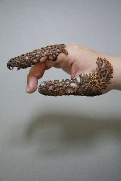 Completion  gloves or ring  wu,ching-chih    I can only climb on your hands to be completed,   yet without your existence I will vanish.   I employ the basic concept of fingers to create a piece which falls in between a ring and a glove,   also combining this form with the growth of vegetation.