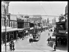Hindley St,Adelaide in South Australia in 1890,from King William St,looking west.On the right, lIsaac's Corner and the Exchange Hotel;on the left are Bridgland & Atterton,Beach's, and Hooper's Furnishing Arcade.