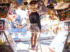 Katrina Tang Photography for Family&Home magazine Tivoli 2013 kids fashion. Girl standing in an amusement park, head hidden into toys, sunny, fun #katrinatang #tangkatrina