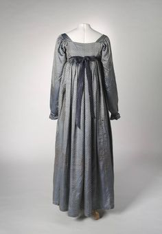 National Museum Australia c. 1810-1815 - silver and blue shot silk with pattern of dark blue flowers; gathered sleeve head, extended cuffs, silk floss corded trim; square back neckline, designed to be worn over a bustle pad; cotton tape drawstring, hand sewn.