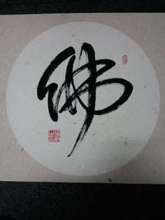 A chinese character BUDDA, written on rice paper with a special calligraphic brush, in one of the many calligraphic styles favored by poets,