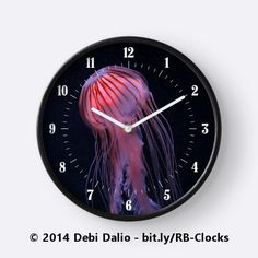 This distinctive round wall clock features a red-striped pink jellyfish floating in a sea of black with its long tentacles hanging down. https://www.redbubble.com/people/debidalio/works/12762006-strawberry-jelly?p=clock #homedecor #wallart #time #animals #sealife #photography #StudioDalio #Redbubble