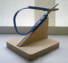 Many of my student have a hard time using scissors (even ones manufactured for students with disabilities) and holding the the paper at the same time. My school's OT department came up with this wood base to mount the scissors on, so that the students just press the top of the loop while they (or the aide) move the paper along.