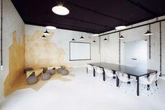 salle de séjour avec un plafond noir, murs en béton, poufs tricotés gris et tables basses en bois