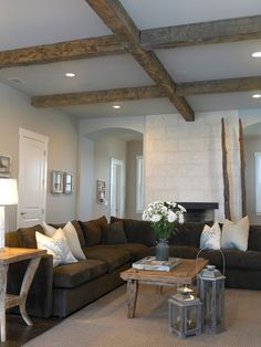 wooden ceiling beams brown lshaped couch fire place grey walls furniture