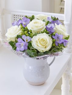 Featuring 5 purple freesias and 5 white large headed roses with green spray hypericum, salal and pittosporum presented in an embossed ceramic jug. Order Flowers Ireland