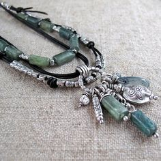 This is a one-of-a-kind piece. A layer of luminous green kyanite and a layer of fine silver beads on knotted black leather cord frame a focal silver