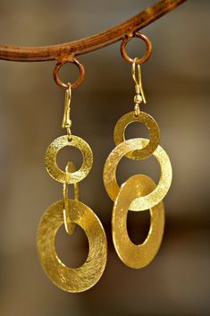 Low key elegance is the name of the game with our Handmade Links Earrings and the best part, they are available in both silver or gold tone!. Fair Trade and handmade textured brass earrings made from three different sized circles, gracefully linked together. Handmade by Fair Trade artisans in India, you'll love the feel of the gorgeous brushed metal against your skin. Available in silver or gold tone and you can pair with the matching necklace for a chic look. The artisans who make our ...