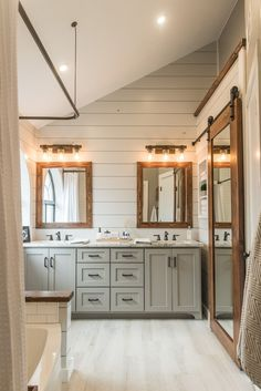 Modern Farmhouse Bathroom Inspiration - Design by Irwin Construction. Painted shiplap walls, reclaimed wood, double vanity, gray green cabinetry, barn door.