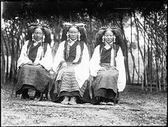 Photographer: Sir Charles Bell or Rabden Lepcha?, Collection: Sir Charles Bell, Date of Photo: May – September 1921, Region: Lhasa.   Three seated women wearing head dresses and charm boxes as part of their costume; seated in one of the parks in Lhasa during a picnic.