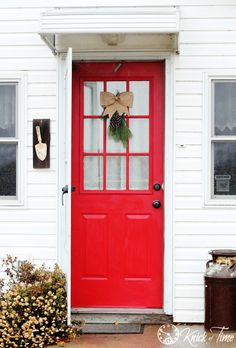 red front door with brown paper bow evergreen wreath - KnickofTime.net