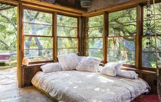 A dreamy bedroom-meets-sunroom with walls of surrounding windows.