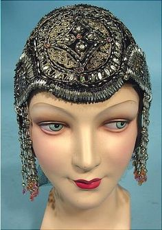 Headdress 1923/1924 Art Deco Flapper Beaded Cloche Full black net cap fully ornamented with gold floss braid, silver and clear beading, and a few great pastel colored beads all in a fabulous deco design.  Complete with long dangle beaded fringe at both sides.