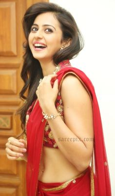"""Actress Rakul preet singh in red net saree at telugu movie """"Tiger"""" audio launch. She was eye catchy in red transparent saree featuring gold sequins border"""