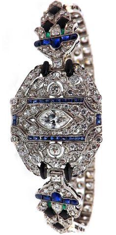 Art Deco platinum, diamond, buff top, emerald, sapphire, black onyx bracelet, 211 round brilliant cut diamonds, 4 emeralds, 32 sapphire, 1925. #ArtDeco #bracelet