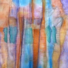 Inktense on Fabric Felt like looking, using blues and oranges. Which are sewn into it.