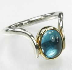 This handmade ring is a combination of silver and 18 carat gold with a stunning cabochon blue topaz. £295.00