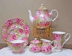 Bone China Lady Diana (Di) Tea Set with service for four. Popular swirled pink Chintz matches pieces. Add gold accents to compliment the gold trim and your tea table is fit for a queen.  Heirloom Fine Bone China Imported from England. Berta Hedstrom.   Includes 6 cup teapot, creamer, sugar, 4 cups and saucers, 4 Dessert Plates, 4 Mugs and gold toned teapot warmer.  Hand wash.