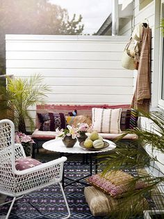 eclectic and cozy outdoor space- i am obsessed with that white chair. and it's from ikea!!!