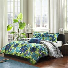 Brighten up your space with the Mizone Jayna Comforter Set. This beautiful floral comforter features an ombre of flowers transforming from large deep blues and purples to smaller outlined flowers at the top of the comforter. The shams also feature printed large bold flowers bringing to motif all the way to the top of the bed. This colorful set is made from a polyester peach skin fabrication that is soft to the touch and machine washable for easy care. One decorative pillow in dark blue with a p…