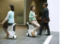 A new personal mobility device from Honda, the Uni-Cub, lets people roll around indoor environments on a single wheel, with a footprint no wider than a pedestrian.