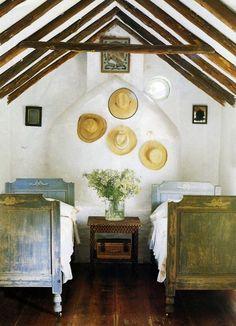 Rustic bedroom | Wooden A-fram ceiling, straw hat wall decor + cozy furniture arrangement