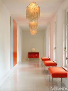 A white hallway with orange benches.