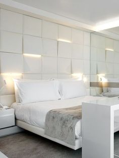 Lighting: uplights and downlights integrated into sculpture squares headboard bedroom wall