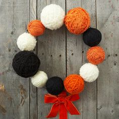 Halloween Yarn Wreath -  This country-chic wreath is a cinch to make. Wrap plastic foam balls of various sizes with orange, cream, and black yarn. Use hot glue to set the end of the yarn in place. Hot-glue each ball to a wire wreath form as desired, adding a pretty orange bow as an accent.