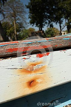 Close up of weathered wooden painted side texture of a small wooden boat, with rust from nails. Tropical trees visible in the background