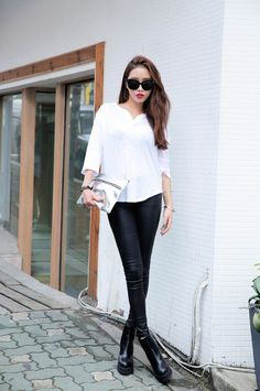 White blouse, black trousers, heels. Silver purse. Sunglasses. Casual street style clothing. Spring fashion