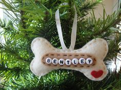 "Make your dog part of the holiday tree this year! Personalized holiday ornament can be used as a present topper or as a special gift to someone in honor of their furry friend. Dog bone measures 3 ¾"" in length by 2"" at the widest end and is made from 100% Recycled Eco Friendly cream, tan and red felt. Hand stitched and hand made, stuffed with polyfil to add shape. Cream colored ribbon is attached for hanging.    This ornament is made to order and will ship within 3 business days. Photo is…"