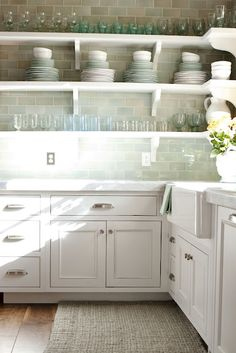 gorgeous kitchen design with white kitchen cabinets marble counter tops farmhouse sink wide plank wood floors blue green glass subway tile backsplash