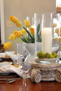 spring tablescape. love the yellow tulips amidst the green reindeer moss, and love this with those huge, bleached-wood-looking pillar holders