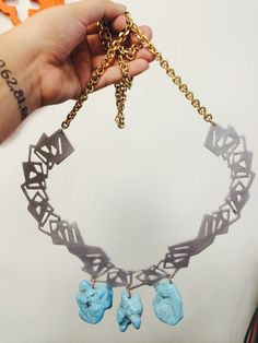 laser cut aluminum w/ gold plated chain and 3 chunks of turquoise.