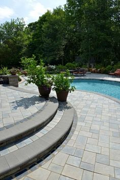 A Concrete Paver Stones Pool Deck And Natural Stone Waterfall Complete This Once Lackluster Backyard