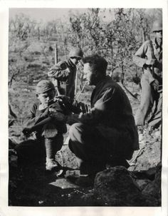 """1944- Bombed out of his home in San Pietro, Italian doctor treats a young refugee boy in a hillside cave """"office""""."""